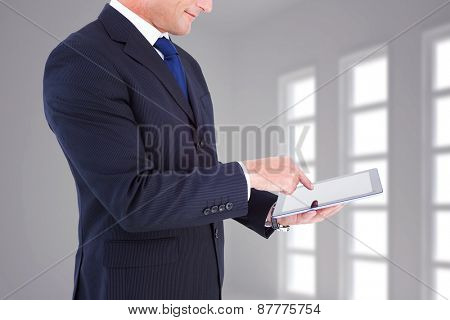 Mid section of a businessman with arms out against dark white room