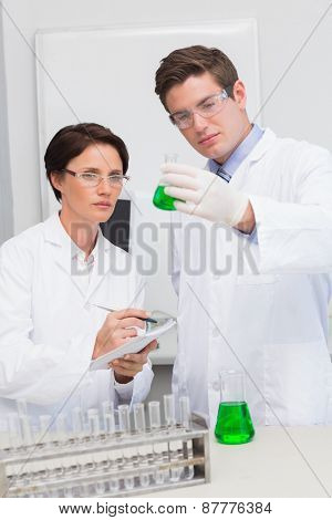 Scientists examining attentively beaker with green fluid in laboratory