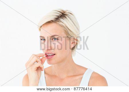 Pretty woman taking pills on white background