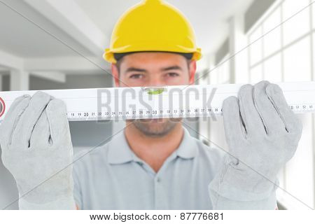 Portrait of handyman holding spirit level against modern white room with window