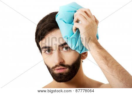 Man with headache and ice bag on his head.