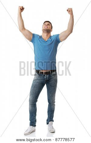 Happy young man with his arms up in victory gesture.