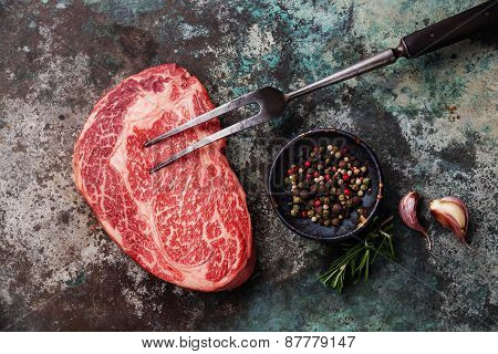 Raw Fresh Marbled Meat Black Angus Steak And Meat Fork On Metal Background