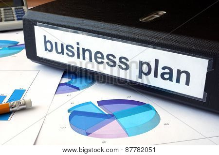 Graphs and file folder with label  Business plan.