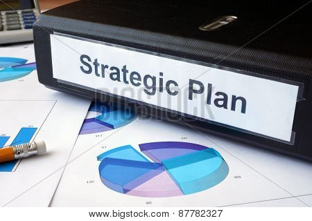 Graphs and file folder with label Strategic plan.