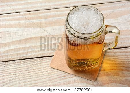 High angle closeup of a mason jar full of beer on a rustic wood table.