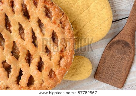 High angle shot of a fresh baked apple pie with lattice crust on an oven mitt. Horizontal format on a rustic white wood kitchen table.