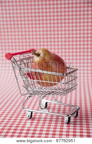 Ripe pear in tiny shopping cart