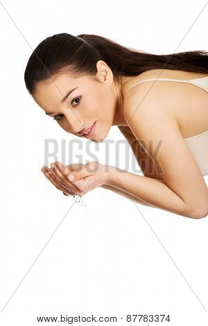 Woman washing her clean face with water.