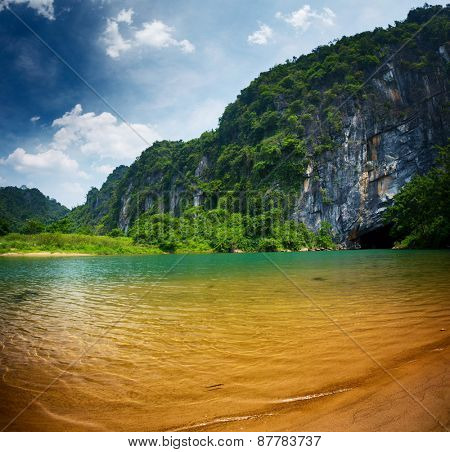 Clear river at sunny day near the entrance to cave of Phong Nha. Vietnam