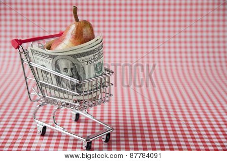 Ripe pear with dollars in tiny shopping cart
