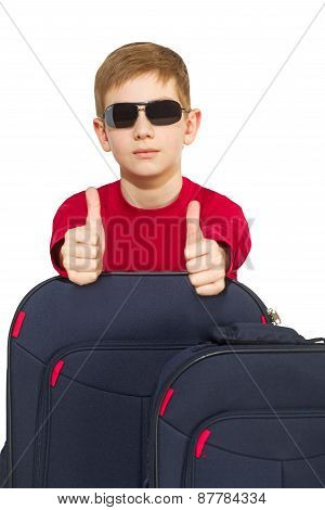 Portrait Of Boy With Travel Bags Wearing Sunglasses Showing Thumbs Up
