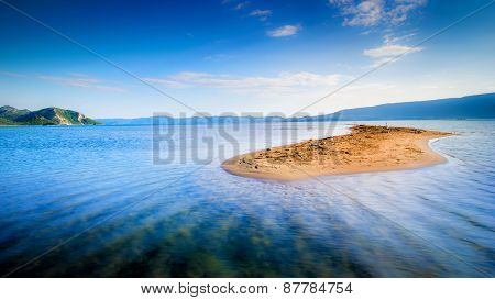 Lone Small Sandy Island In The Middle Of Blue Sea