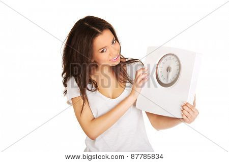 Happy african woman holding a scale.
