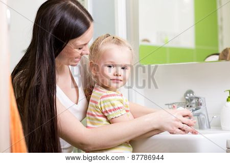 Happy Mother And Daughter Washing Hands At Home In Bathroom