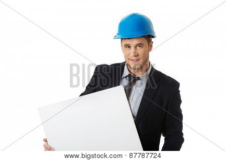 Handsome businessman in hard hat holding empty banner.