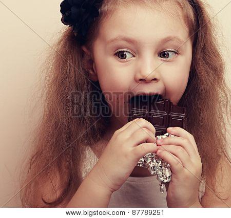Thinking Kid With Fun Look Eating Dark Chocolate. Vintage