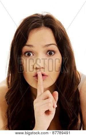 Young woman with finger on lips gesturing silent sign.