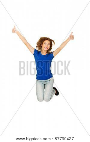 Young beautiful happy woman jumping with thumbs up.