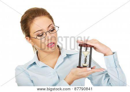 Beautiful businesswoman holding a sandglass.