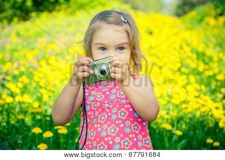 Little girl taking pictures with point and shoot camera