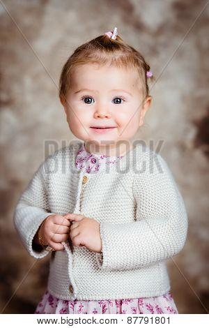 Portrait Of Sweet Blond Little Girl With Big Grey Eyes And Plump Cheeks