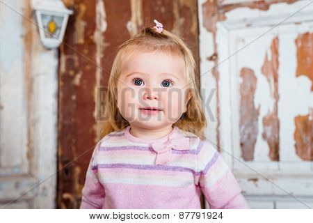 Surprised Funny Blond Little Girl With Big Grey Eyes And Plump Cheeks Looks Up. Studio Portrait