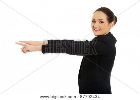 Beautiful businesswoman pointing on empty space.