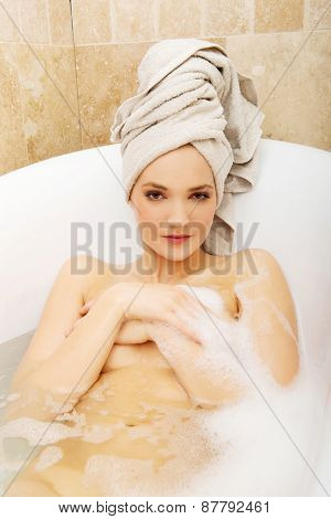 Young spa woman relaxing in bathtub.