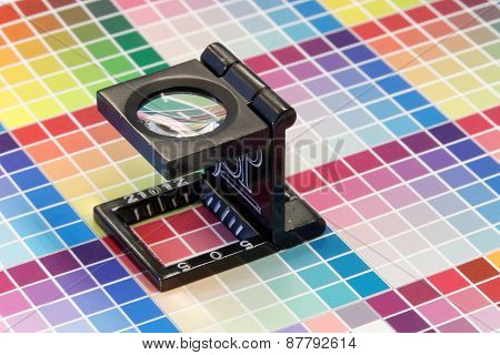Close-up Of A Loupe On A Colorful Test Print