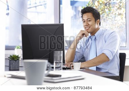 Happy young Asian businessman working with computer, sitting at desk in bright office.