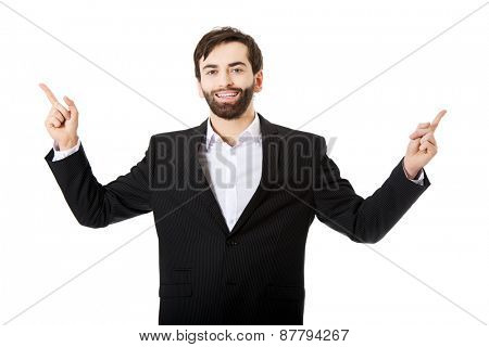 Happy young businessman points his finger up.