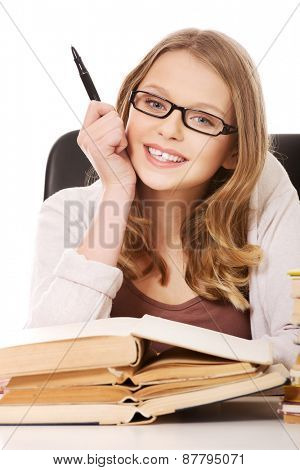 Happy teenage woman with stack of books