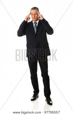 Full length pensive businessman touching head.
