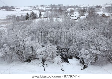 Russian winter. Snow-covered landscape with the village of Kruppsk near the Izborsk Fortress near Pskov, Russia.