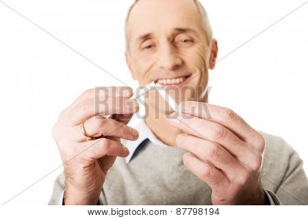 Successful mature man with broken cigarette.