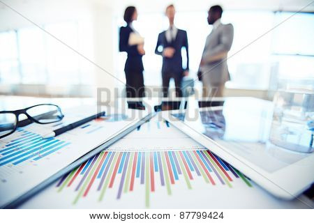 Business documents and touchpad with charts on desk