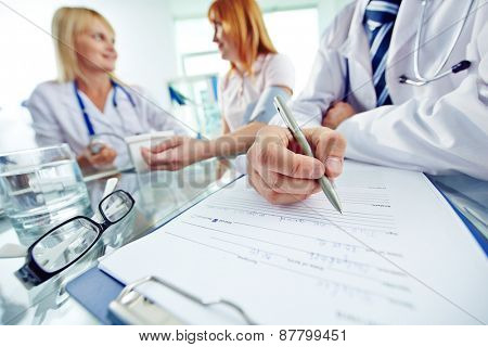 Close-up of doctor with pen filling in personal data