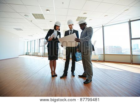 Group of architects discussing blueprint in office