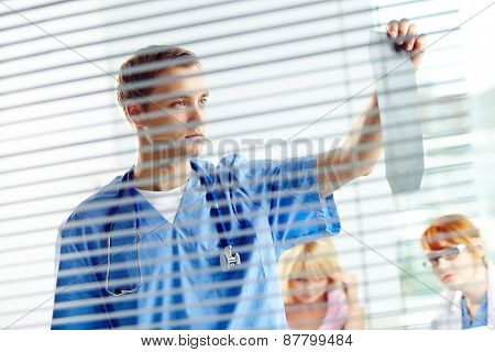 Young doctor looking at x-ray in office