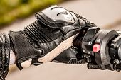 stock photo of motorcycle  - Human hand in a Motorcycle Racing Gloves holds a motorcycle throttle control - JPG