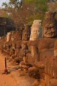foto of demons  - Stone Asura demons hold the naga serpent king Vasuki on the bridge entrance to Angkor Thom Cambodia - JPG