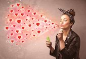 pic of blowing  - Pretty young girl blowing valentine red heart symbols  - JPG
