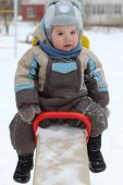 picture of seesaw  - Little boy wearing warm jumpsuit sits on seesaw at winter day - JPG