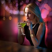 picture of bitchy  - Young attractive woman looking around leaning on the bar counter while sipping her cocktail - JPG