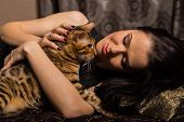 picture of bengal cat  - Young beautiful brunette holding a Bengal cat - JPG