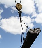 picture of reinforcing  - crane lifts and moves a pack with metal reinforcement against the sky with clouds - JPG