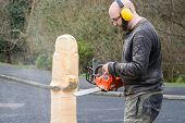 stock photo of man chainsaw  - The making of an owl sculpture by a chainsaw sculptor here in the early stages - JPG