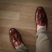 image of loafers  - Sockless male legs in tasseled loafers dark leaf colored and burnished - JPG