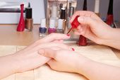 stock photo of nail  - Manicurist doing manicure client painting nails with red nail polish in salon on yellow towel  - JPG